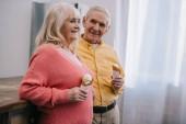 s úsměvem starší pár se drží kornouty na zmrzlinu doma s kopií prostor