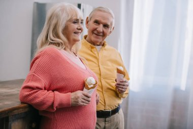 smiling senior couple holding ice cream cones at home with copy space