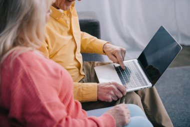 cropped view of senior couple sitting and using laptop with blank screen at home