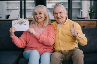 senior couple showing thumb up sign while holding envelope with 'roth ira' lettering and dollar banknotes