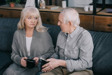 upset senior couple sitting on couch and holding wallets at home