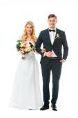 krásná nevěsta v bílých svatebních šatech a pohledný ženich v černém obleku izolované na bílém