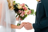 cropped view of bride with beautiful wedding bouquet, and groom holding hands isolated on white
