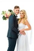 mosolygó menyasszony, esküvői csokor, átölelve boldog vőlegény elszigetelt fehér