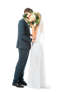 Bride in long wedding dress, and groom in elegant suit embracing while hiding faces behind wedding bouquet isolated on white stock vector