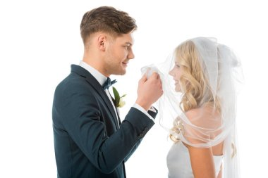 happy groom looking at smiling brides face while lifting bridal veil isolated on white