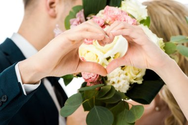 Selective focus of groom and bride showing heart sign with hands, while hiding faces behind wedding bouquet isolated on white stock vector