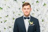 pohledný ženich v elegantní sako s boutonniere na bílém květinové pozadí při pohledu na fotoaparát