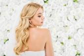vonzó fiatal nő, szőke haj, pózol a kamera fehér virágos háttér