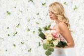 Fotografie krásná mladá nevěsta drží na bílém pozadí květinové svatební kytice