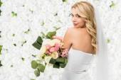 schöne junge Braut Brautstrauß halten und Blick in die Kamera auf weißen Blumen Hintergrund