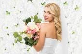 gyönyörű fiatal menyasszony, esküvői csokor gazdaság és látszó-on fényképezőgép-fehér virágos háttér