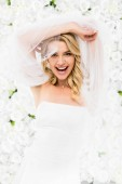 cheerful young bride holding bridal veil in raised hands on white floral background
