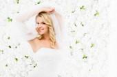 Fotografie Happy krásná nevěsta drží v rukou na bílém pozadí květinové svatební závoj