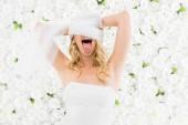 Fotografie nadšený mladá nevěsta svatební závoj kolem hlavy vinutí na bílém pozadí květinové