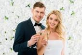 Fotografia giovani coppie che clinking i vetri di champagne e che guarda lobbiettivo su fondo floreale bianco