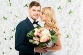 šťastný mladý ženich a nevěsta drží na bílém pozadí květinové svatební kytice