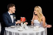 happy handsome groom presenting red gift box to surprised bride, while sitting at served table isolated on black