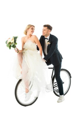 Happy bride with wedding bouquet sitting on bicycle together with smiling groom isolated on white stock vector