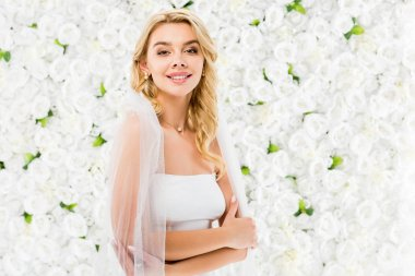 Happy beautiful bride with blonde hair posing at camera on white floral background stock vector