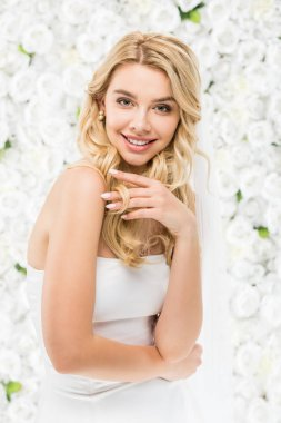 happy young bride with blonde hair posing at camera on white floral background
