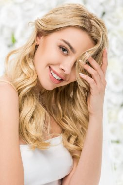 smiling attractive girl with blonde hair posing at camera on white floral background