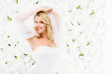 happy beautiful bride holding bridal veil in raised hands on white floral background