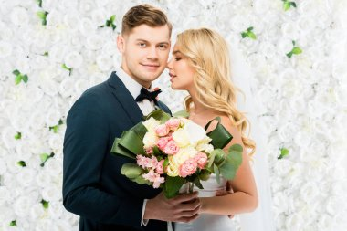 happy young bride and groom holding wedding bouquet on white floral background