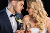 Fotografia Coppie felici che si siede in faccia e tintinnio di bicchieri di champagne isolato sul nero