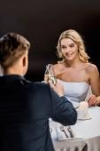 Fotografia messa a fuoco selettiva della bella sposa e dello sposo tintinnio di bicchieri di champagne su fondo nero