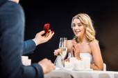 selective focus of man making marriage proposal to beautiful girl on black background
