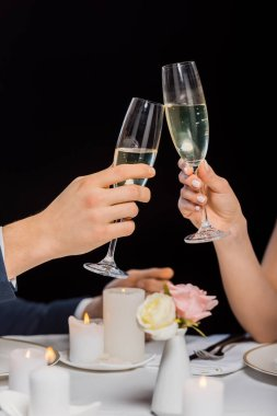 cropped view of man and woman holding glasses of champagne isolated on black