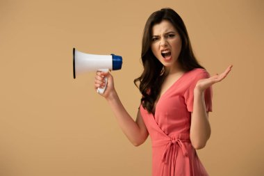 Angry brunette woman in dress holding megaphone and screaming isolated on beige