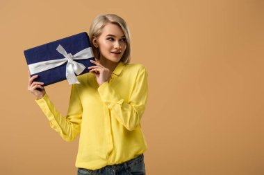 Curious young woman in yellow shirt holding gift box with ribbon isolated on beige stock vector