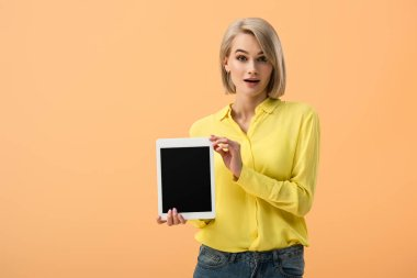 Surprised girl in yellow shirt holding digital tablet with blank screen isolated on orange stock vector