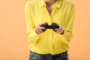 Cropped view of woman in yellow shirt holding gamepad isolated on orange stock vector
