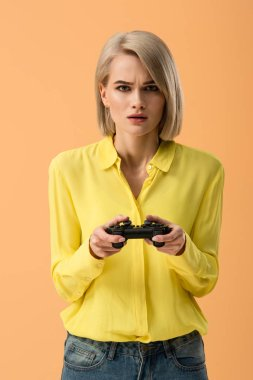 Worried blonde woman in yellow shirt holding gamepad isolated on orange stock vector