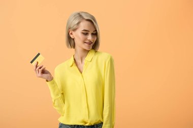 Charming blonde woman in yellow shirt holding credit card isolated on orange