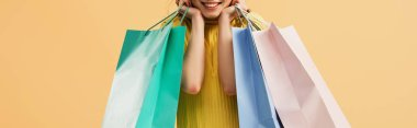 Panoramic shot of laughing girl holding shopping bags isolated on orange