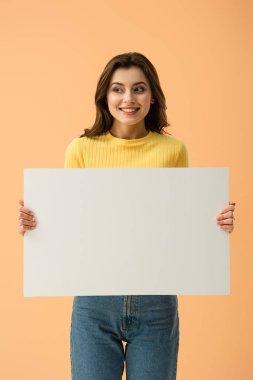Blissful smiling brunette girl holding blank placard isolated on orange stock vector