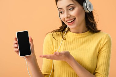 Happy brunette girl in headphones showing smartphone with blank screen isolated on orange