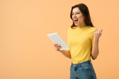 Excited brunette girl holding digital tablet and laughing isolated on orange