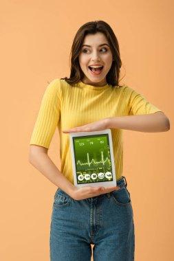 Joyful brunette woman holding digital tablet with health app on screen isolated on orange stock vector