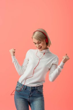 cheerful blonde woman listening music in headphones and gesturing isolated on pink