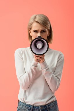 blonde young woman speaking in megaphone isolated on pink