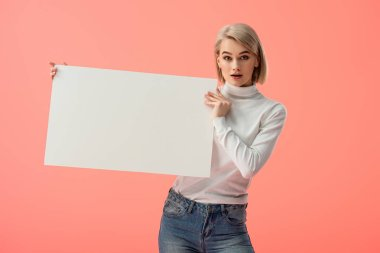 Surprised blonde girl holding blank placard isolated on pink stock vector