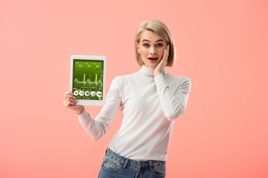 Surprised blonde woman holding digital tablet with health app on screen isolated on pink stock vector