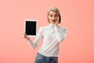 Shocked blonde woman holding digital tablet with blank screen isolated on pink stock vector