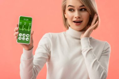 Selective focus of surprised blonde woman holding smartphone with health app on screen isolated on pink stock vector