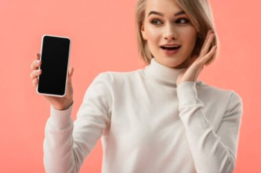 Selective focus of shocked young blonde woman holding smartphone with blank screen isolated on pink stock vector